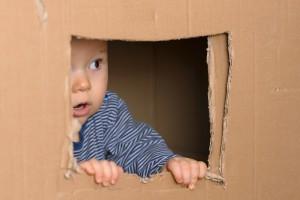 staunendes Baby schaut vorsichtig aus Fenster
